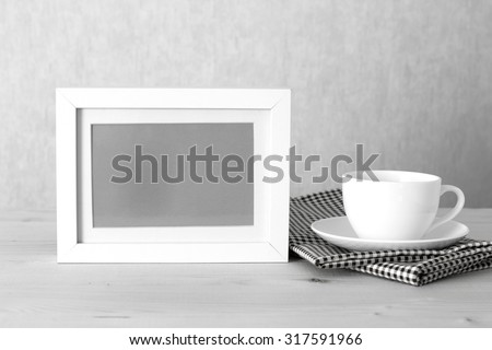 Photo frame and coffee cup on table cloth on wooden table - vintage effect style picture
