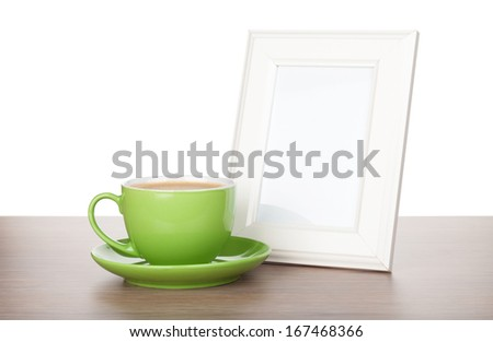 Photo frame and coffee cup on wooden table. Isolated on white background