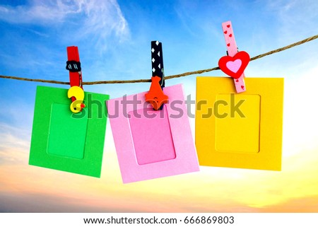 Photo Frame hanging on the rope with sky background.