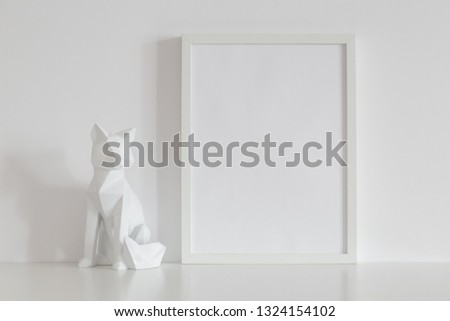 Photo frame mock up and origami fox design home decor on a white table.