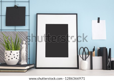 Photo frame mock up on a blue wall and home office supplies. #1286366971