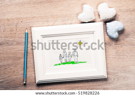 Photo frame with happy family drawing on wooden table