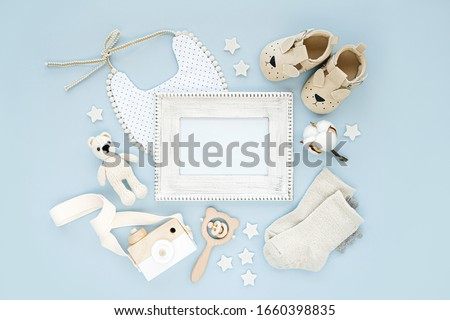 Photo frame with set of clothes and accessories fot newborn boy. Toys, socks and baby slippers with bib on blue background. Mock up tor text.  Flat lay, top view  Stock fotó ©