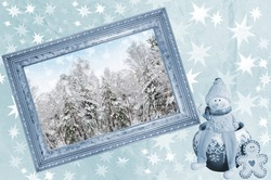 Photo frame with winter landscape and Christmas tree toys on blue, crumpled paper in the stars. The concept of winter holidays