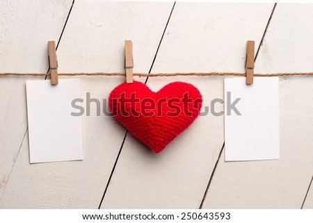 Photo frames and valentines day toy heart hanging on rope. Isolated on white wooden background