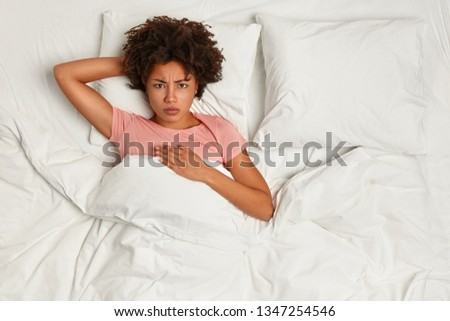 Photo from above of Afro American woman awakes in angry mood, has bad dreams at night, stays in bed ill, displeased to have spoiled plans, wears domestic clothing, poses in bedroom after slumber #1347254546