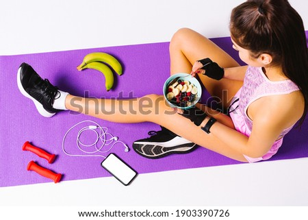 Photo from above. Sportive girl with muesli m fruit taler after workout sitting on the mat with headphones, phone and dumbbells. Fitness and healthy food concept. Stock fotó ©