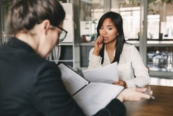 Photo from back of businesswoman interviewing and reading resume of nervous female applicant during job interview - business, career and placement concept