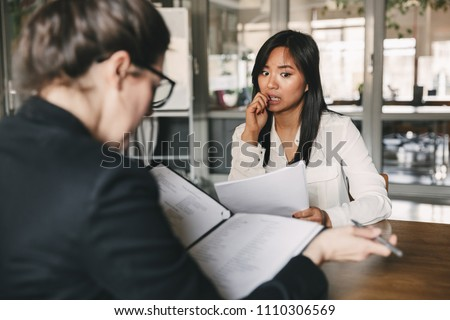 Photo from back of businesswoman interviewing and reading resume of nervous female applicant during job interview - business, career and placement concept #1110306569