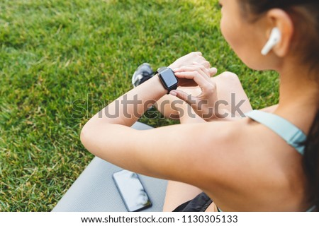 Photo from back of caucasian fitness woman 20s in sportswear resting in green park and looking at wrist watch with bluetooth earphone