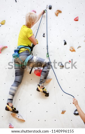 Stock Photo Photo from back of sports girl in yellow T-shirt clambering up wall