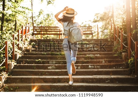 Photo from back of young woman 18-20 wearing summer clothes and straw hat running up stairs in green park on sunny day