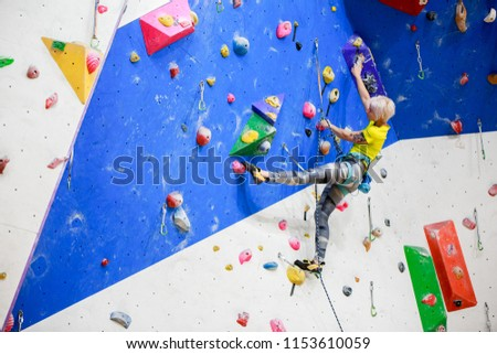 Stock Photo Photo from below of young girl exercising on climbing wall