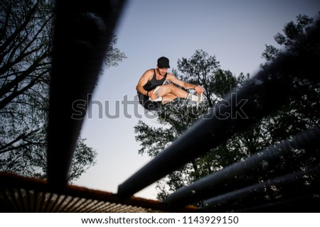 Photo from below young man in the cap jumping on the trampoline on the background of tree and beautiful evening sky