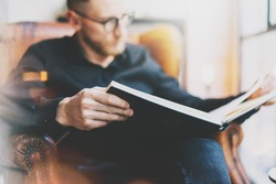 Photo handsome bearded scientist wearing glasses black shirt.Man sitting in vintage chair university library, reading book and relaxing. Blurred background.Horizontal, film effect.