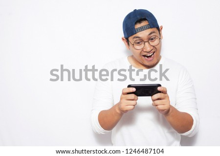 Photo image portrait of a cute handsome young Asian man with funny face playing games on tablet smart phone