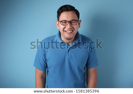 Photo image portrait of funny young attractive cute Asian man smiling happily, against blue background
