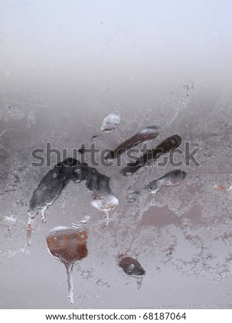 Photo impression of a human hand on icy glass