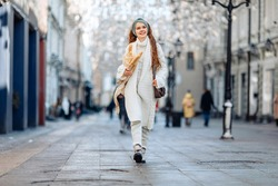 Photo in motion. Girl in an all-white knit outfit with bag on shoulder returns from French bakery with several baguettes in hands. Satisfied smile and a glance away. Advertising of bakery products.