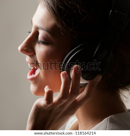 Photo in profile expressive girl in headphones singing emotionally