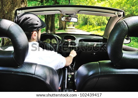 Photo inside of a sports car driving through park