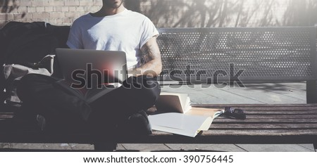 Photo man sitting city park bench and using laptop wireless internet. Studying at the University, working new project. Using book, generic design computer. Wide