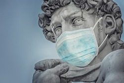 Photo manipulation about Michelangelo's David statue (Florence, Italy) protecting himself from coronavirus (COVID-19) with a surgical mask
