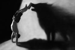 Photo-manipulation - handstand in studio with wolf shadow