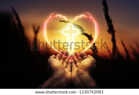 photo manipulation of worshipping hands  wuth glow cross and heart of flame on sunset background, worship faith hope prayer christian concept