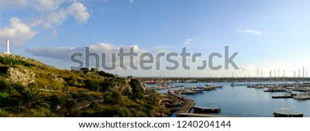 Photo merge: Boats moored in the marina of Leuca in Italy, in the background the cliff and the lighthouse on a beautiful sunny day at