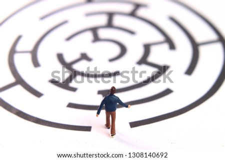 Photo miniature figur toy young man walking into labyrinth, face the challenges to achieve goals