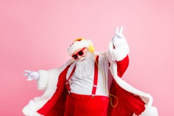 Photo modern funky santa claus listen x-mas christmas stereo radio use headphones raise hands fingers wear style stylish big belly costume pants headwear isolated pastel color background