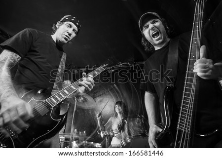 Photo of a band playing on stage. Male guitarist, male bassist and female drummer. Shot with strobes and slow shutter speed to create lighting atmosphere and blur effects. Slight motion blur visible.