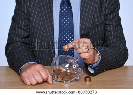 Photo of a banker sat at his desk putting coins into his piggy bank.