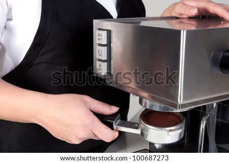 Photo of a barista putting a porta-filter full of freshly ground coffee into an espresso machine.