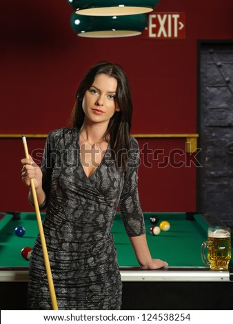 Photo of a beautiful brunette holding a pool cue and leaning up against a pool table.