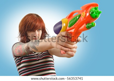 Photo of a beautiful redhead about to shoot a water gun.