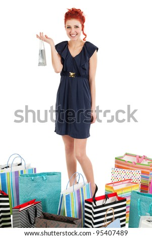 Photo of a beautiful redhead girl standing with many shopping bags around her feet over white background.