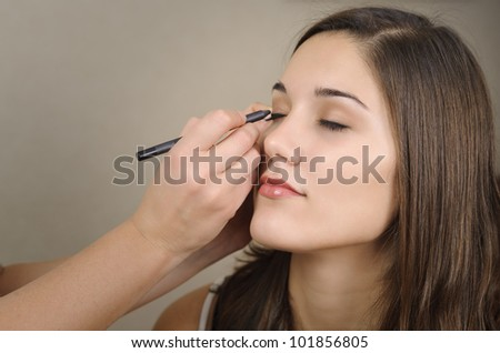 photo of a beautiful woman while being makeup