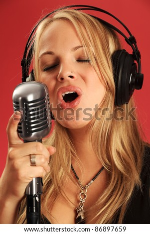 Photo of a beautiful young blond wearing headphones and singing into a vintage microphone.