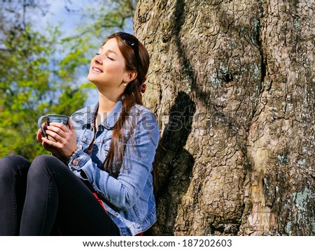 Photo of a beautiful young woman enjoying the warmth of the sun in early spring while she drinks her coffee.