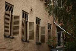Photo of a beige wall of a house with four open windows with wooden shutters. Windows on the other wall without shutters. The foliage of the tree is visible from the side.