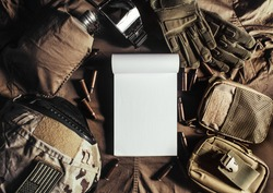 Photo of a blank notebook laying on military table with helmet, glasses, bullet shells, gloves and flask upper view.
