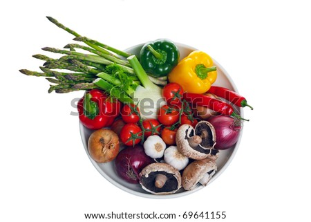 Photo of a bowl of vegetables shot from above and isolated on a white background, part of the ingredients for a mediterranean meal.