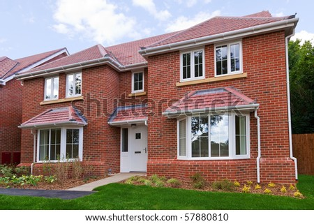 Photo of a brand new unoccupied detached red brick built five bedroom house on a modern housing development.