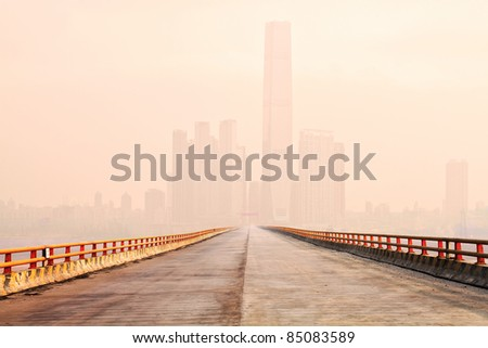 Photo of a bridge leading to the downtown of an international modern city in the fog morning