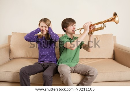 Photo of a brother playing his trumpet too loudly, or badly, and annoying his sister.