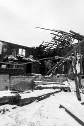 Photo of a burnt house in winter. Charred beams of a wooden house. Burned down house.