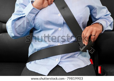 Photo of a business woman sitting in a car putting on her seat belt