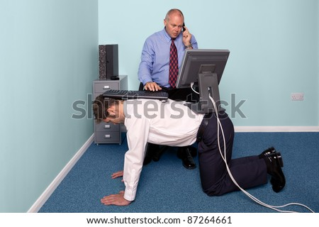 Photo of a businessman using a work experience employee for his desk